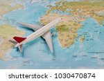 white toy plane on the world... | Shutterstock . vector #1030470874