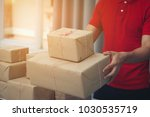 handsome deliver male in red... | Shutterstock . vector #1030535719