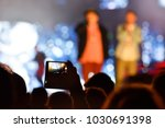 man at a concert shooting video ... | Shutterstock . vector #1030691398