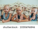 Small photo of Little Boys and Girl Eating Ice-Cream at Home