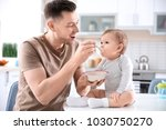 father feeding his little son... | Shutterstock . vector #1030750270