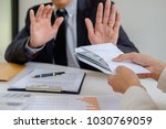 Small photo of Businessman refusing money in the envelope to agreement contract, Bribe and corruption concept