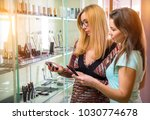 two women look at the window... | Shutterstock . vector #1030774678