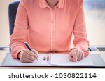young female is writing notes... | Shutterstock . vector #1030822114