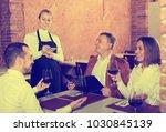 pretty female waiter writing... | Shutterstock . vector #1030845139
