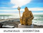 Small photo of Yellow sculpture of Neptune with a trident on the Black Sea coast in sunny Sochi and a pigeon on his head
