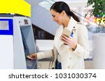 woman withdrawing cash at an atm | Shutterstock . vector #1031030374