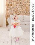 Small photo of Little baby girl in white lavish dress standing in living room in house on sofa and wooden wall background and holding a bunch of toy plastic keys in red.