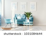 Small photo of Palm on light blue, round table standing next to a rocking chair and sofa in bright living room interior