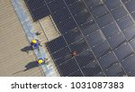 workers on the roof clean solar ...   Shutterstock . vector #1031087383