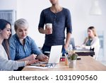 Small photo of Businesswomen working together on a new campaign using laptop in an advertising agency