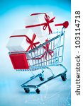 Small photo of shopping cart ahd gift on blue background