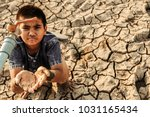 Small photo of Sad a boy sitting on cracked earth open metal water old faucet on hot and dry empty land. Affected of global warming made climate change. Water shortage and drought concept.