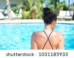 a girl at the poolside at her... | Shutterstock . vector #1031185933
