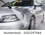 Detail on car front being washed with jet water in carwash. - stock photo
