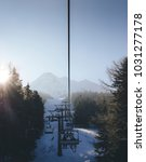 Small photo of Sun through pine trees as chairlift ascent at Italian ski area covered in snow - winter sports concept