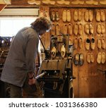 Small photo of Professional clog maker in Holland - clogs lined up on wall