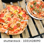 two pizzas on wooden table...   Shutterstock . vector #1031428090