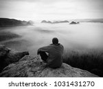 Small photo of Hiker on the rocky peak. Wonderful daybreak in mountains, heavy creamy mist in deep valley. Man on the summit. Black and white photo.