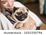 Stock photo young woman with cute pug dog at home pet adoption 1031550796