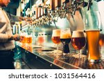 Stock photo we meet oktoberfest hand of bartender pouring a large lager beer in tap pouring beer for client 1031564416
