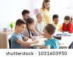 teachers helping children with... | Shutterstock . vector #1031603950
