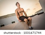 muscular young man sitting on... | Shutterstock . vector #1031671744