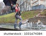 girl with umbrella outdoor in a ... | Shutterstock . vector #1031674384