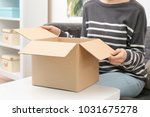 woman with parcel box indoors | Shutterstock . vector #1031675278