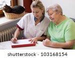 Blond Nurse Visiting A Senior...