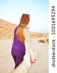 Small photo of Back of an athlete lady dragging the hand of her love to an adventure in the desert of Wadi Rum