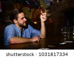 macho sits in bar with empty... | Shutterstock . vector #1031817334