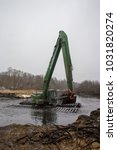 Small photo of Balashikha, Moscow area, Russia - December 14, 2017: The floating excavator removes silt from the Pekhorka river bed
