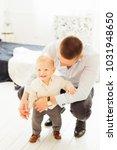 father sat down near a little... | Shutterstock . vector #1031948650