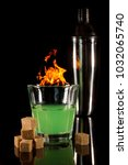 Small photo of A glass with absinth on a black reflecting surface