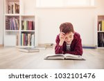 Small photo of Eight years old child lying on the floor among books at home. Serious boy reading in white room