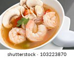 Thai shrimp soup bowl close up with mushrooms and vegetables. - stock photo