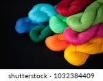 Small photo of Bright thread in skeins, yarn in bright colors, set of yarn on black background, cotton, linen, flax, skein, yarn