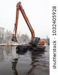 Small photo of Balashikha, Moscow area, Russia - December 19, 2018: The floating excavator cleans the Malashka river bed from silt and garbage