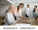 Small photo of Young team leader correcting offended senior employee working on computer in office, female manager scolding aged old worker for mistake or incompetence, different generations and age discrimination