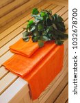 Small photo of Birch tree birch and orange towel in a light Finnish sauna