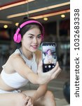 beautiful asian girl listening... | Shutterstock . vector #1032683338