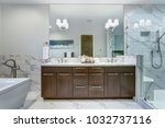 Incredible master bathroom with Carrara marble tile surround, modern glass walk in shower, espresso dual vanity cabinet and a freestanding bathtub.   - stock photo
