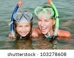 Summer beach - lovely girls diver in the sea - stock photo