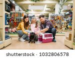 Stock photo family buying supplies for little puppy in petshop 1032806578