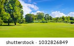 Small photo of Summer park with deciduous trees and broad lawns. In the blue sky, light cumulus clouds. Wide photo.