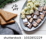 Stock photo herring fish with potatoes slices and red onion rye bread on the white table top view 1032852229