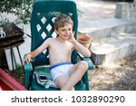 cool kid boy sitting in chair... | Shutterstock . vector #1032890290