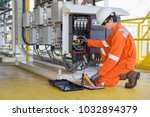 Electrical and instrument technician measuring voltage of thermo electric generator and record reading value to maintenance sheet for annual inspection at offshore oil and gas remote platform. - stock photo