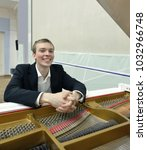 Small photo of Smiling young man behind white grand piano